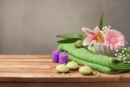 aroma: Spa and wellness concept with fresh towel, candles and flowers on wooden table over rustic background