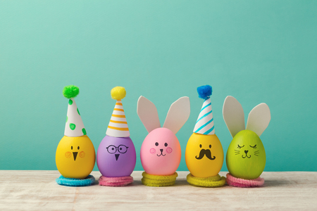 Easter holiday concept with cute handmade eggs, bunny, chicks and party hats