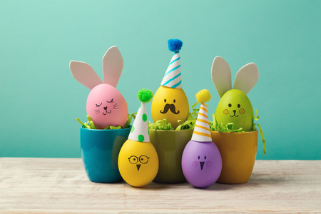 Easter holiday concept with cute handmade eggs in coffee cups, bunny, chicks and party hats Archivio Fotografico
