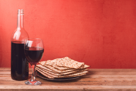 Passover holiday concept with wine glass and matzoh on wooden table over red background Stock Photo