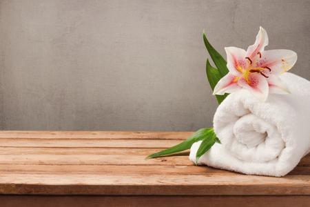 스파와 웰빙 개념 하얀 수건와 소박한 배경 위에 나무 테이블에 꽃