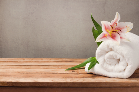 Spa and wellness concept with white towel and flower on wooden table over rustic background Stockfoto