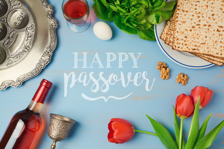 Passover holiday greeting card with seder plate, matzoh, tulip flowers and wine bottle on wooden background. Top view from above