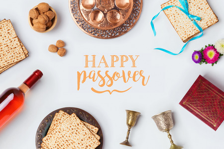 Jewish holiday Passover Pesah greeting card with wine, matza and seder plate. View from above. Flat lay