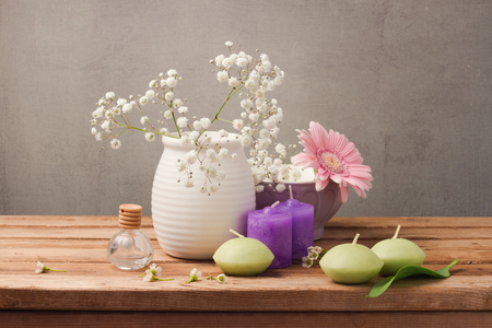 flowers in vase: Spa and wellness concept with flowers in vase and candles on wooden table over rustic background Stock Photo