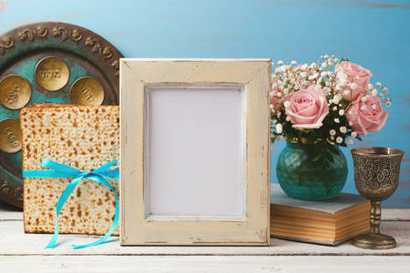 Jewish holiday Passover Pesah concept with poster photo frame, matzoh and rose flowers bouquet