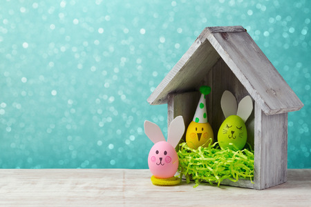 holiday house: Easter holiday concept with cute handmade egg and bird house over bokeh background