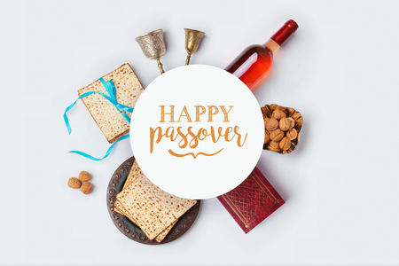 Jewish holiday Passover banner design with wine, matza and seder plate on white background. View from above. Flat lay