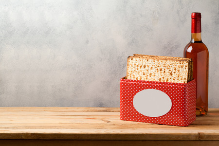 Passover celebration concept with matzoh and wine bottle on wooden table over bright background with copy space Stock Photo