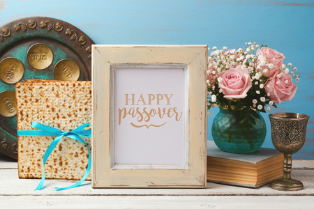 matzoh: Jewish holiday Passover Pesah concept with poster photo frame, matzoh and rose flowers bouquet