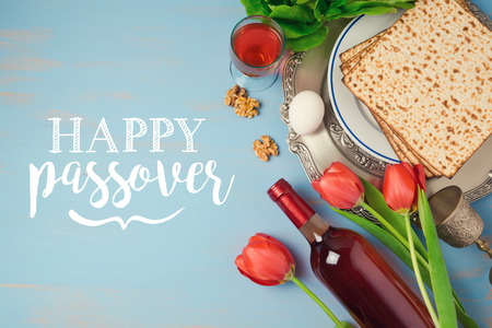 matzoh: Jewish holiday Passover Pesah greeting card with seder plate, matzoh and flowers over blue background. View from above