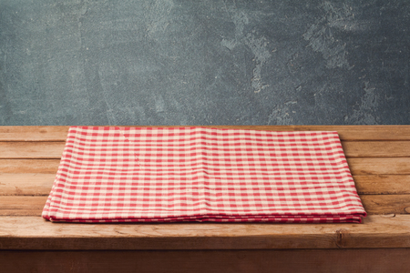 kitchen furniture: Empty wooden deck table with checked tablecloth over blackboard background for product montage display