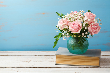 feminine background: Rose flower bouquet in vase on old books over wooden background with copy space