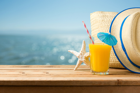 Summer holiday vacation concept with orange juice, hat and bag over sea beach background 스톡 콘텐츠