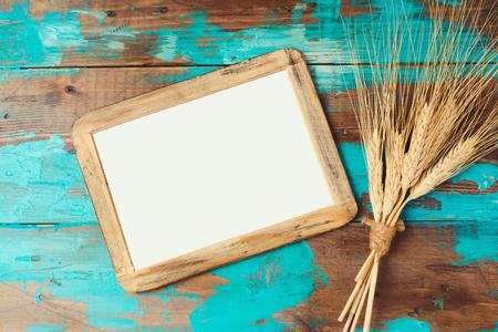 cultivo de trigo: Marco de carteles y cosecha de trigo sobre fondo de madera. Concepto Shavuot del día de fiesta judío. Vista desde arriba