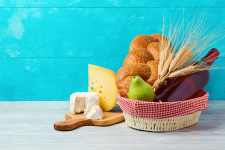 Basket with wine bottle, bread and cheese on wooden table. Jewish holiday Shavuot concept.