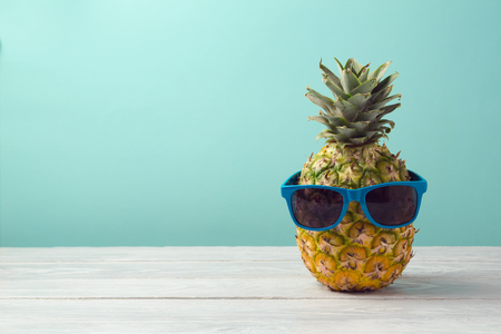 Pineapple with sunglasses on wooden table over mint background. Tropical summer vacation and beach party concept. Banco de Imagens