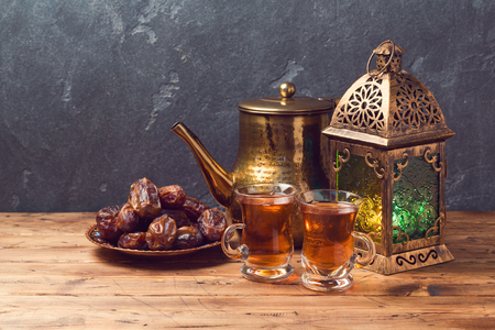 Lightened lantern, tea cups and dates on wooden table over blackboard background. Ramadan kareem holiday celebration concept