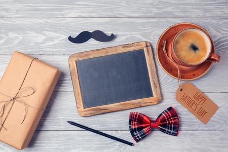 与黑板,咖啡杯和礼物盒的父亲节背景在木桌上。从以上观点。平躺