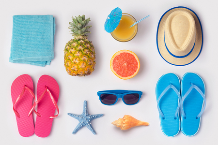 Tropical summer vacation concept with pineapple, juice and flip flops organized on white background. View from above. Flat lay Archivio Fotografico