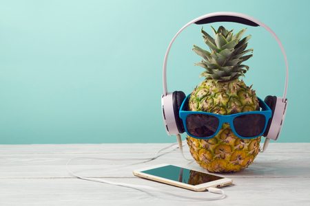 Pineapple with sunglasses, headphones and smart phone on wooden table over mint background. Tropical summer vacation and beach party concept.