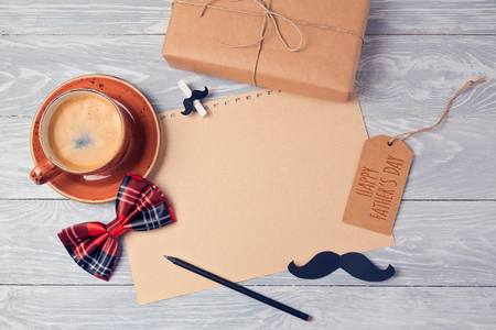 Fathers day background with paper, coffee cup and gift box on wooden table. View from above. Flat lay Archivio Fotografico