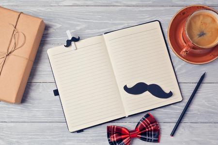 父亲节背景笔记本,咖啡杯和礼品盒放在木桌上。从以上观点。平躺