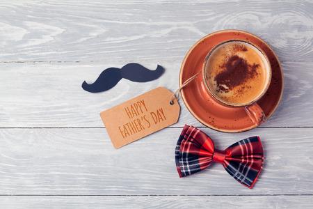 De achtergrond van de vadersdag met koffiekop, nota en boog op houten lijst. Uitzicht van boven. Plat leggen