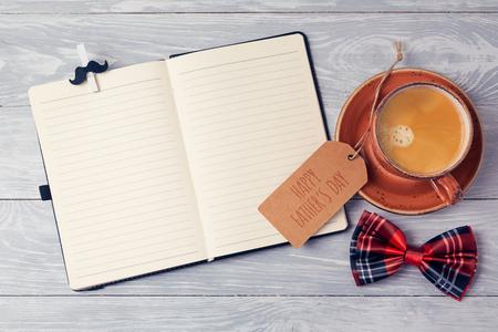 与笔记本,咖啡杯和弓的父亲节背景在木桌上。从以上观点。平躺股票照片