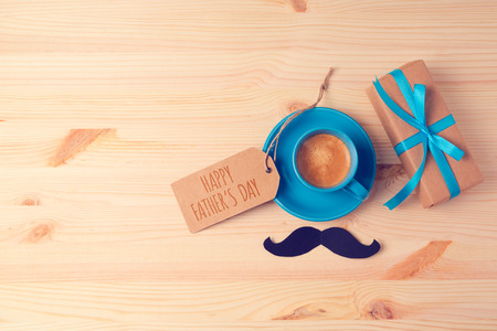Fathers day background with coffee cup and gift box on wooden table. View from above. Flat lay Foto de archivo
