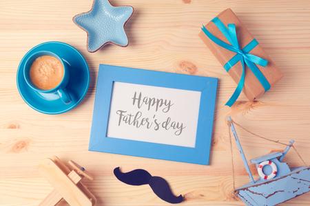 与照片框架,咖啡杯和礼物盒的父亲节背景在木桌上。从以上观点。平躺股票照片
