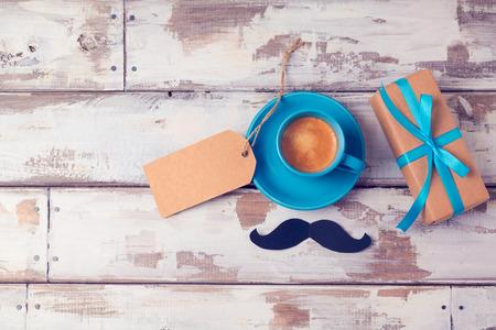 与咖啡杯和礼物盒的父亲节背景在木桌上。从以上观点。平躺股票照片