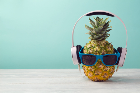 Pineapple with headphones and sunglasses on wooden table over mint background. Tropical summer vacation and beach party concept.