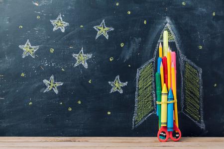 칠판 배경 위에 연필 로켓으로 학교 개념 돌아 가기
