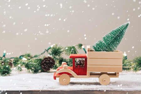 Christmas tree on toy truck over festive background. Christmas holiday celebration concept