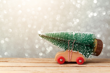 Christmas holiday concept with toy car and pine tree over bokeh background Stock Photo