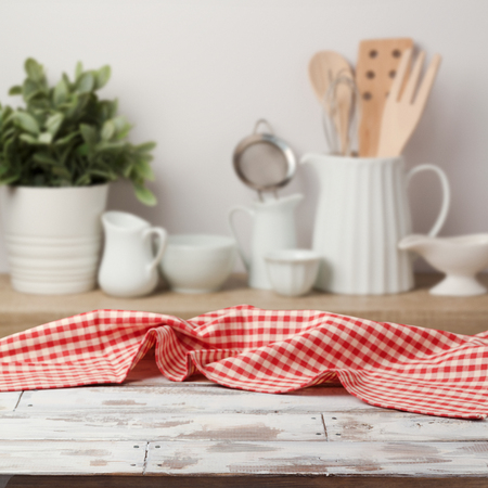 Empty wooden table with red checked tablecloth over kitchen shelf background