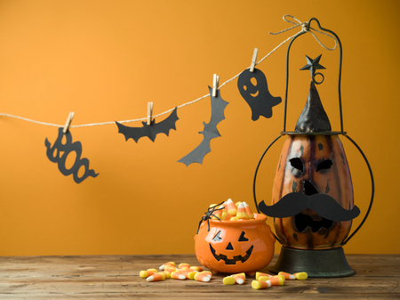 Halloween background with decor jack o lantern and candy corn on wooden table
