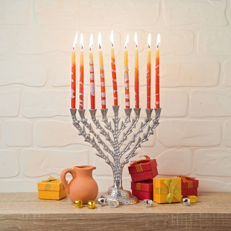Jewish holiday Hanukkah celebration with menorah, gift box and dreidel on wooden table over brick wall background
