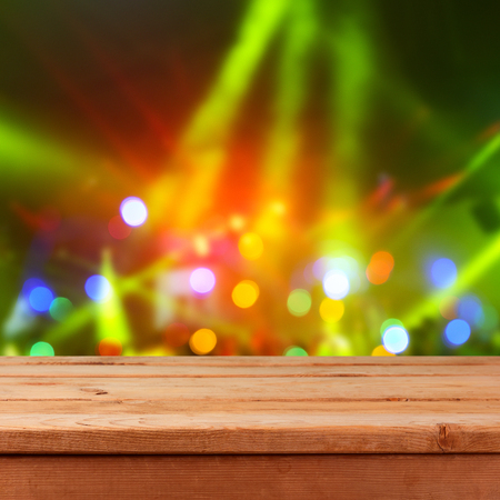 Christmas and new year party concert background with empty wooden table and lights bokeh Stock Photo