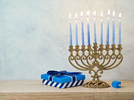 Hanukkah celebration with menorah, gift box and dreidel on wooden table over bright background