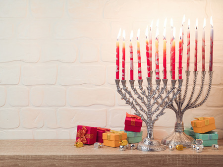 Jewish holiday Hanukkah background with menorah and gift boxes