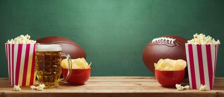 Amerikaans voetbal het letten op concept met popgraan en spaanders over groene achtergrond Stockfoto