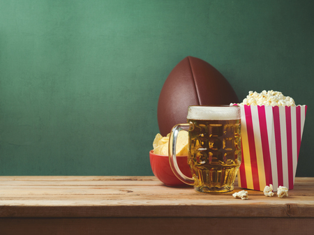 American football watching concept with beer, pop corn and chips over green background Stock Photo