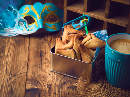 Hamantaschen cookies in box over rustic background with coffee cup. Purim holiday celebration.
