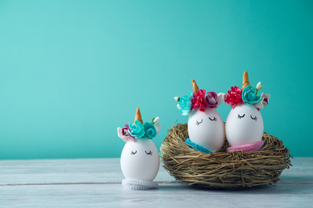 Easter holiday concept with cute handmade eggs, unicorns decor in bird nest