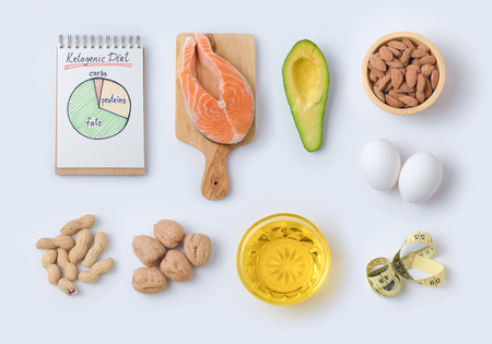 Ketogenic low carbs diet concept. Healthy eating and dieting with salmon fish, avocado, eggs and nuts. Top view. Flat lay