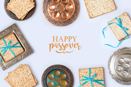 Jewish holiday Passover frame composition with matzo and seder plate on white background. View from above. Flat lay.Translation for Hebrew Text: Passover, horseradish, celery, egg, bone, bitter herb, charoset - paste made of fruits Stock Photo