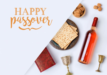 Jewish holiday Passover banner design with wine, matzo and seder plate on white background. View from above. Flat lay