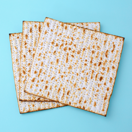 Matzo for Passover celebration over blue background. Top view